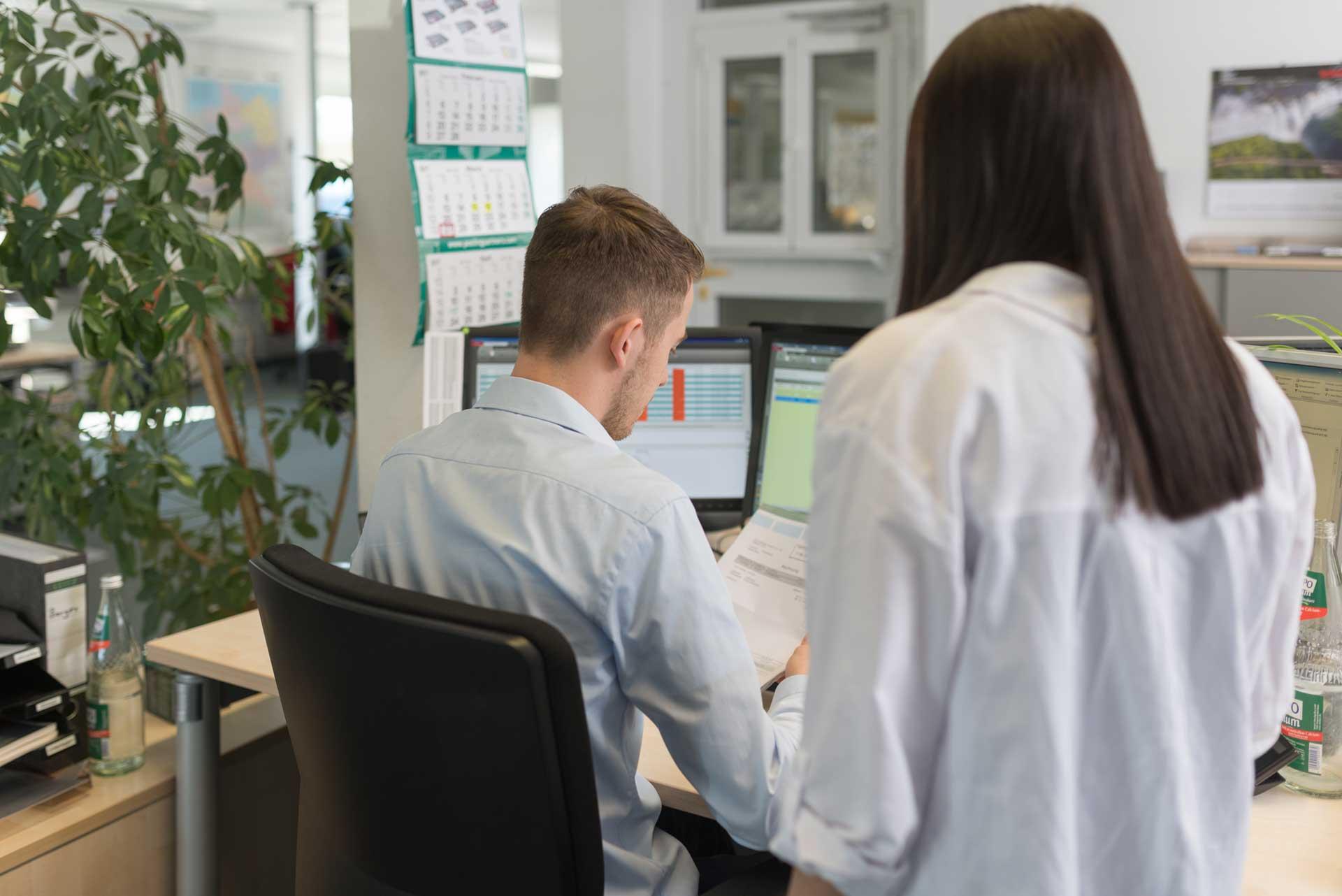 Mitarbeiter sitzen an Rechner und prüfen Kundenanfrage